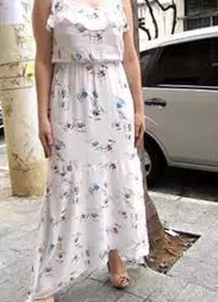 Vestido longo off white de alcinha com estampa de flores e barra assimétrica.