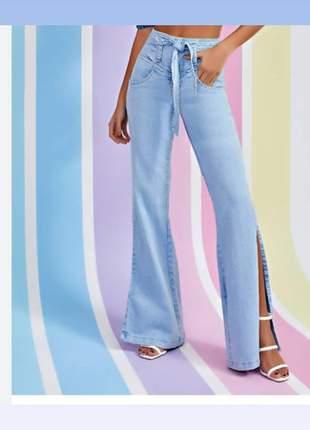 Calça jeans claro com cinto e fendas nas laterais da perna cintura alta.