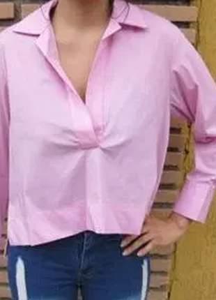 Blusa com recorte curto na frente e alongado atrás, com mangas longas, gola e punho.