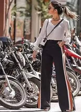 Calça pantalona com listras na laterais.