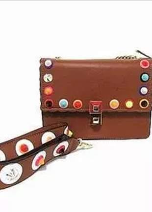 Bolsa com aplicações e alça estilizada.