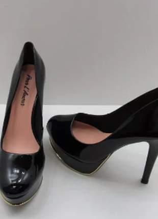 Sapato feminino meia pata verniz preto com bico amendoado e detalhe dourado.
