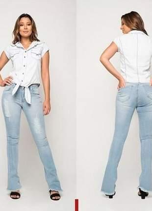 Calça jeans feminina elaborada em lavagem clara, modelo destroyed e barra flare