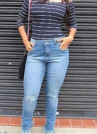 Calça jeans feminina elaborada em lavagem clara, modelo destroyed, barra desfiada