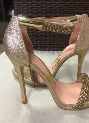 Sandália festa salto alto fino dourada com glitter e strass, detalhe fechamento dourado.